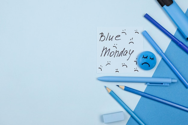 Widok z góry na smutną twarz z ołówkami na niebieski poniedziałek z miejsca na kopię