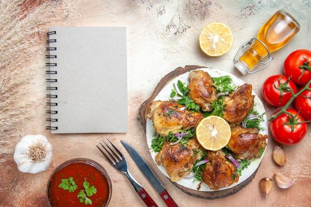 Widok z góry na sos z kurczaka, olej, pomidory, czosnek, cytryna, kurczak z ziołami, widelec, nóż, notatnik