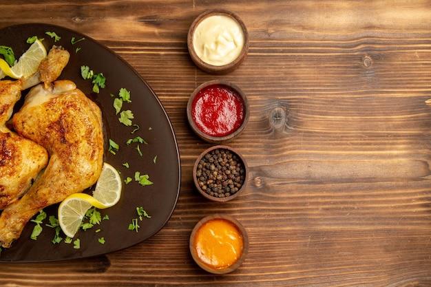 Widok z góry na sosy i miski z kurczaka z kolorowymi sosami czarny pieprz i frytki oraz talerz udek z kurczaka z ziołami i cytryną na stole
