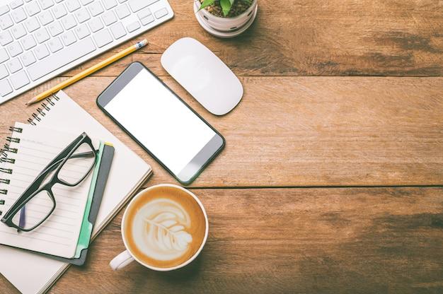 Widok z góry na sprzęt biurowy, w tym laptop, telefon komórkowy, mysz, notebook, filiżankę kawy na drewnianej podłodze
