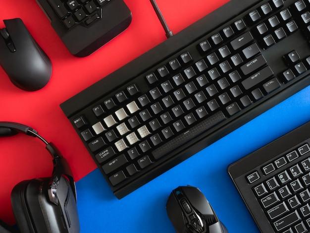 Widok z góry na sprzęt do gry, mysz, klawiaturę, słuchawki i podkładkę pod mysz na tle stołu.