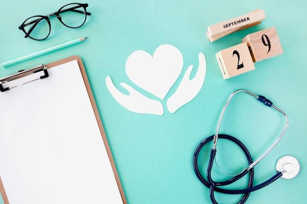 Widok z góry na stetoskop z notatnikiem i papierowym sercem