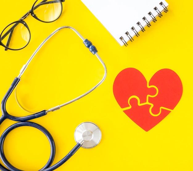 Widok z góry na stetoskop z notatnikiem i sercem układanki