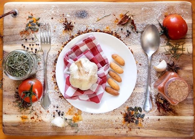 Widok z góry na stół kuchenny, talerz z główką czosnku na czerwonej szmatce, w towarzystwie dressingów