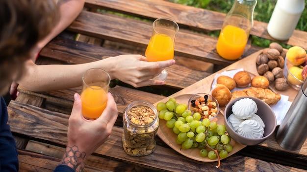 Widok z góry na stół pełen jedzenia i napojów, mężczyzna i kobieta biorący go. glamping