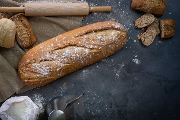Widok z góry na stół roboczy obok piekarnika z bochenkiem chleba i kilkoma świeżymi bułkami
