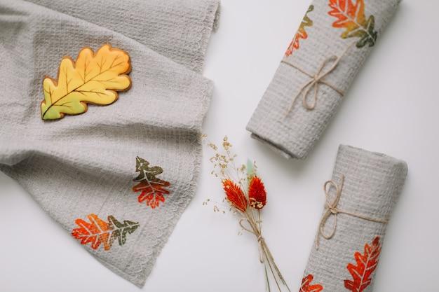 Widok z góry na stół z lnianymi ręcznikami kuchennymi z jesiennymi liśćmi i kwiatami