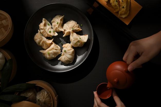 Widok z góry na stół z pierożkami dimsum i kobiecą ręką z dzbankiem do herbaty w chińskiej restauracji