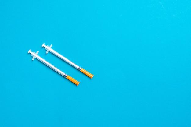 Widok z góry na strzykawki insulinowe gotowe do wstrzyknięcia na kolorowej powierzchni