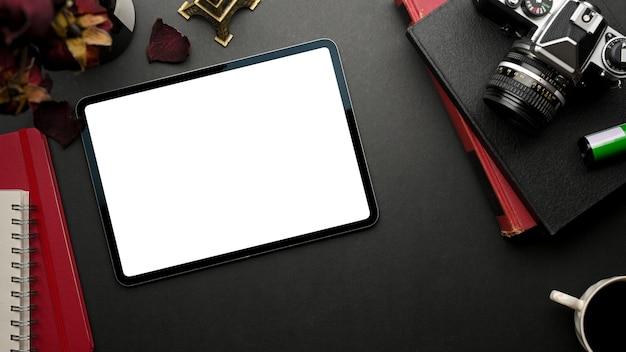 Widok z góry na stylowy, płaski obszar roboczy z cyfrowym tabletem, aparatem i notebookami, ścieżką przycinającą