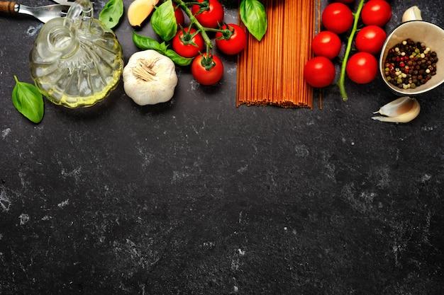 Widok z góry na suchy makaron i świeże pomidory czereśniowe na ciemnym kolorze czarnym