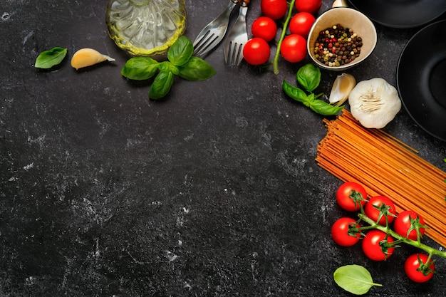 Widok z góry na suchy makaron i świeże pomidory czereśniowe