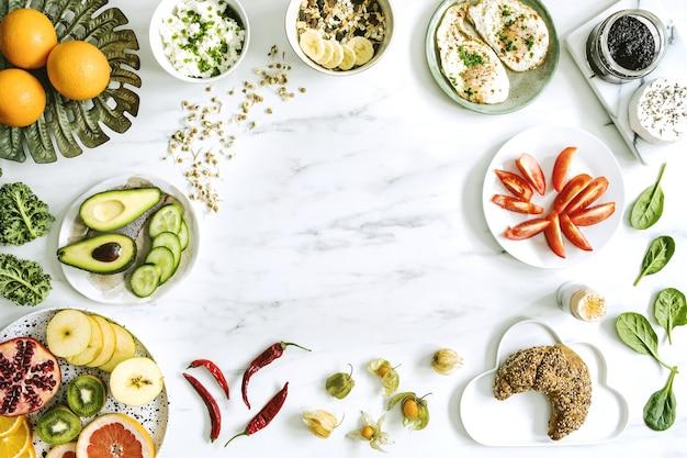 Widok z góry na super jedzenie na białym marmurowym stole. leżał płasko. różne składniki warzywne i zdrowa żywność dla wegetarian. stół śniadaniowy. skopiuj miejsce. szablon.