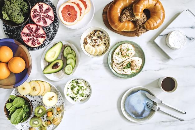 Widok z góry na super jedzenie na białym marmurowym stole. leżał płasko. różne składniki warzywne i zdrowa żywność dla wegetarian. stół śniadaniowy.