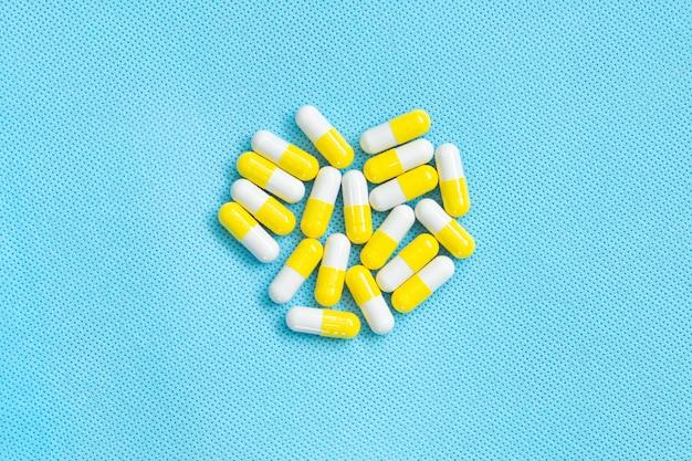Widok z góry na suplementy witaminowe. pojęcie medyczne. żółto-białe pigułki na niebieskim tle
