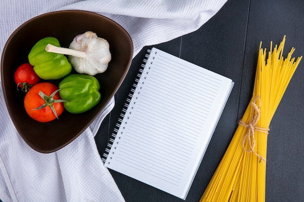 Widok z góry na surowe spaghetti z pomidorami, czosnkiem i papryką w misce na białym ręczniku i notatniku na czarnej powierzchni