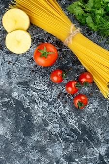 Widok z góry na surowy makaron z ziemniakami, pietruszką i pomidorami na jasnoszarej powierzchni