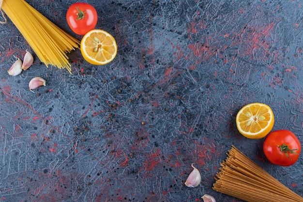 Widok z góry na surowy makaron ze świeżymi czerwonymi pomidorami i czosnkiem na ciemnym tle.