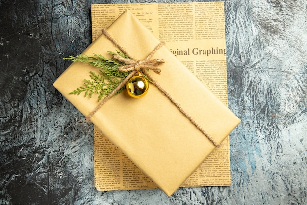 Widok z góry na świąteczny prezent na gazecie sosnowa zabawka świąteczna na szarej powierzchni
