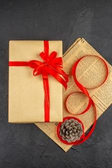 Widok z góry na świąteczny prezent w brązowej papierowej wstążce na gazecie na ciemnej powierzchni