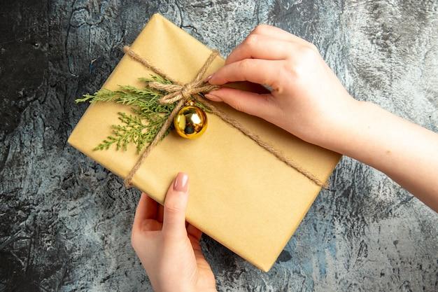 Widok z góry na świąteczny prezent w kobiecych rękach na szarej powierzchni