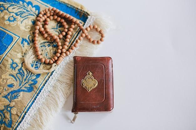 Widok z góry na świętą księgę al koran na macie modlitewnej i koraliki modlitewne z miejscem na kopię jest arabska litera, która oznacza świętą księgę