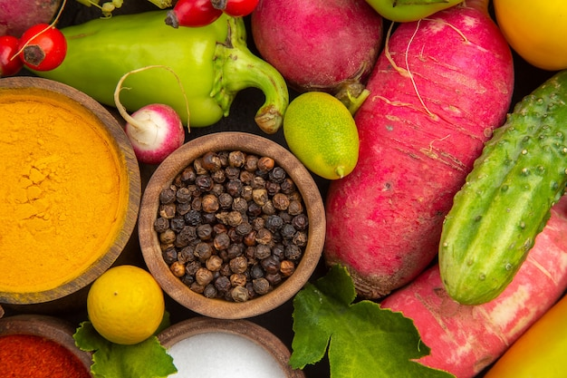 Widok z góry na świeżą kompozycję warzywną z przyprawami na ciemnej dojrzałej sałatce zdrowe życie jedzenie dieta posiłek kolor