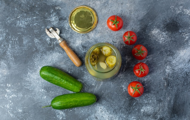 Widok z góry na świeże i marynowane warzywa. otwarty słoik marynat ze świeżym pomidorem i ogórkiem