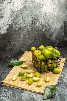 Widok z góry na świeże kumkwaty i cytryny w czarnym koszu na gazetach na szarym tle obrazu stockowego