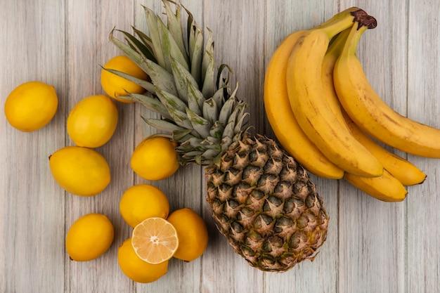 Widok z góry na świeże owoce, takie jak ananas, banany i cytryny, odizolowane na szarej drewnianej powierzchni