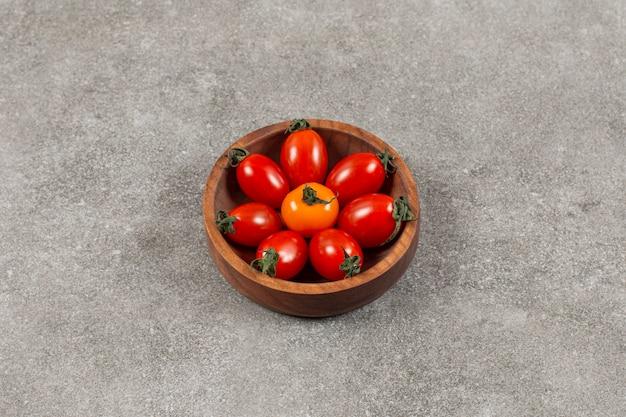Widok z góry na świeże pomidory czereśniowe w drewnianej misce.