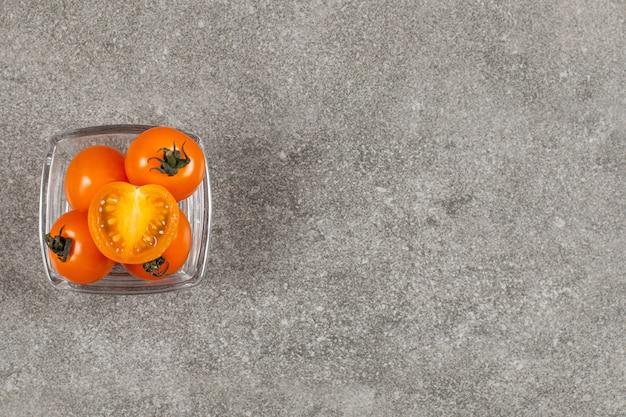 Widok z góry na świeże pomidory czereśniowe w szklanej misce.