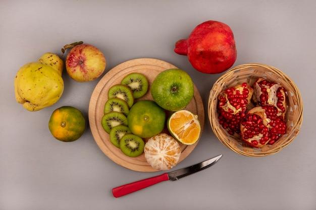 Widok z góry na świeże posiekane plasterki kiwi na drewnianej desce kuchennej z zielonym jabłkiem i mandarynką z granatową pigwą i żółtym jabłkiem na białym tle