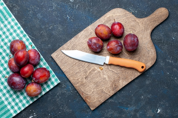 Widok z góry na świeże śliwki, całe łagodne i soczyste na ciemnym biurku, świeże owoce jagodowe
