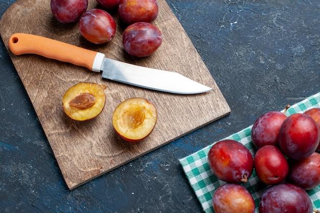 Widok z góry na świeże śliwki, całe łagodne i soczyste na ciemnym biurku, świeże owoce witaminowe lato