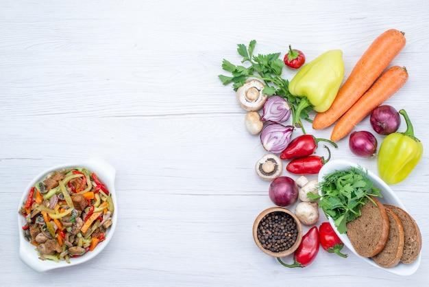 Widok z góry na świeże warzywa, takie jak cebula papryka marchewka z bochenkami chleba na lekkim biurku, witamina mączki z warzyw