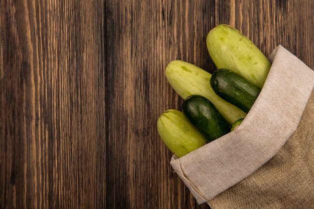 Widok z góry na świeże warzywa, takie jak ogórki i cukinie, w jutowym worku na drewnianej powierzchni z miejscem na kopię