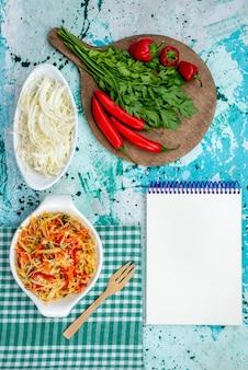 Widok z góry na świeże warzywa wraz z notatnikiem z sałatką z czerwonej ostrej papryki i kapustą na jasnoniebieskim, warzywnym zielonym posiłku spożywczym