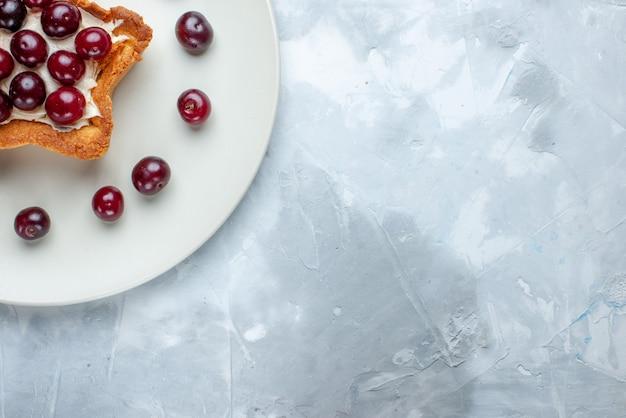 Widok z góry na świeże wiśnie wewnątrz talerza z kremowym ciastem w kształcie gwiazdy na jasnobiałym tle