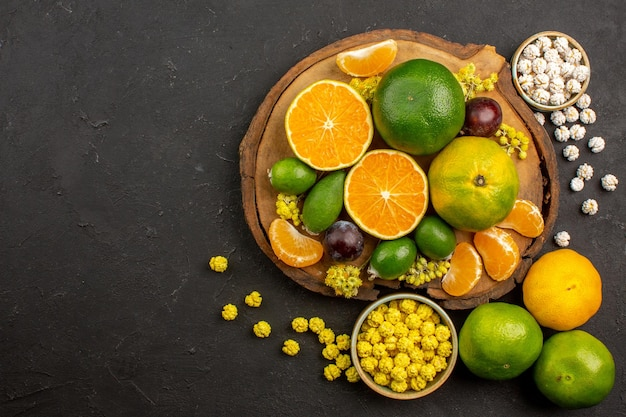 Widok z góry na świeże zielone mandarynki z feijoas i cukierkami w ciemności