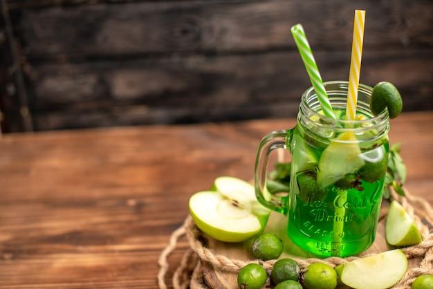 Widok z góry na świeży pyszny sok owocowy podany z jabłkiem i feijoa na drewnianej desce do krojenia