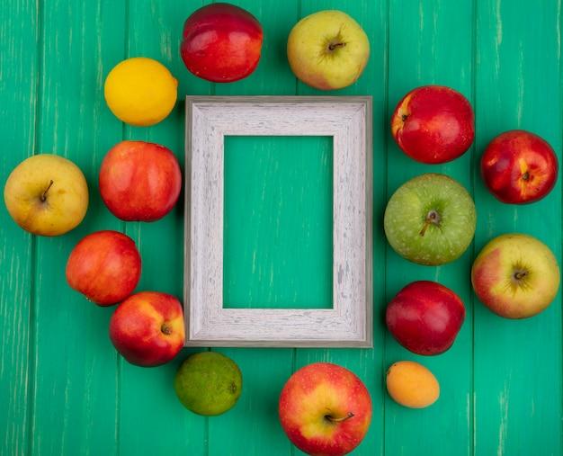 Widok z góry na szarą ramkę z brzoskwiniami, jabłkami i cytryną z limonką na zielonej powierzchni