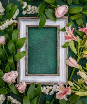 Widok z góry na szarą ramkę z jasnoróżowymi kwiatami na zielonej powierzchni