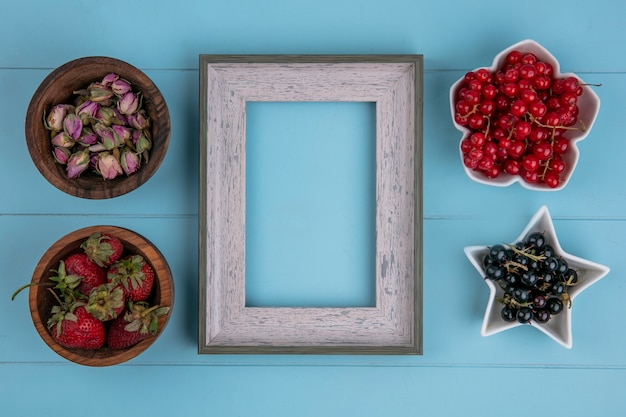 Widok z góry na szare ramki z suszonymi pąkami róży, truskawkami i czerwonymi i czarnymi porzeczkami na niebieskiej powierzchni