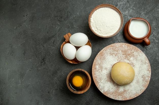 Widok z góry na szarej przestrzeni składniki na ciasto, mleko, jaja i mąka