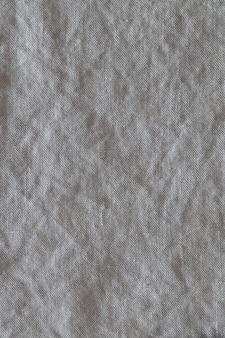 Widok z góry na szarym tle gniecionej tkaniny lnianej. zbliżenie ręcznik, serwetka, obrus lub odzież.