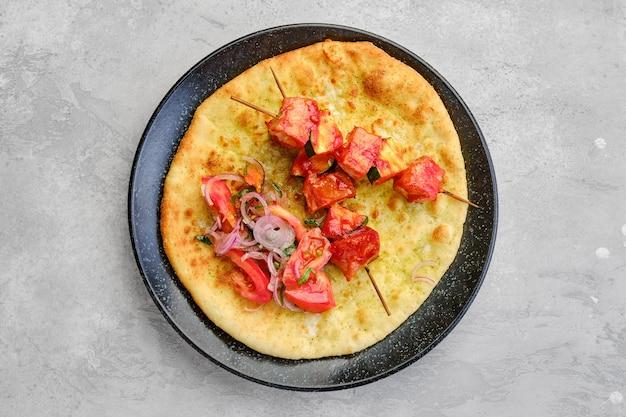 Widok z góry na szaszłyk podany na tortilli z pomidorem i czerwoną cebulą
