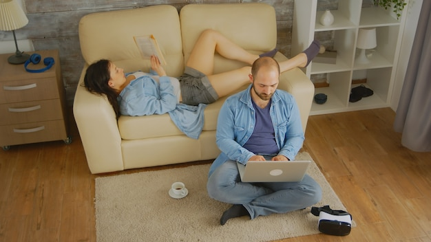 Widok z góry na szczęśliwą młodą parę w jasnym pokoju rozkoszującym się wolnym czasem