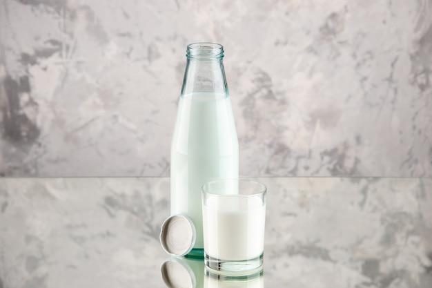 Widok z góry na szklaną butelkę i kubek wypełniony nakrętką mleczną na tle pastelowych kolorów z wolną przestrzenią