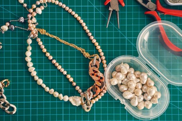 Widok z góry na szklane koraliki, perłowe koraliki, złote elementy i szczypce na zielonym tle